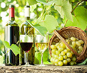 bottles with glasses and grapes